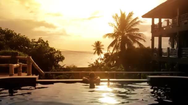 Luftaufnahme des Luxus Hote, entspannende junger Mann im Pool unter Palmen in traumhaften Sonnenuntergang. 1920 x 1080