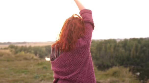 Beautiful red haired woman enjoying nature on a field dancing, spinning and laughing outdoors during amazing sunset. Slow motion, 4K, 3840x2160