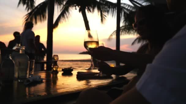 Silueta mladý pár cinkání sklenic s bílým vínem v kavárně beach na úžasný západ slunce. HD, 1920 × 1080. Zpomalený pohyb