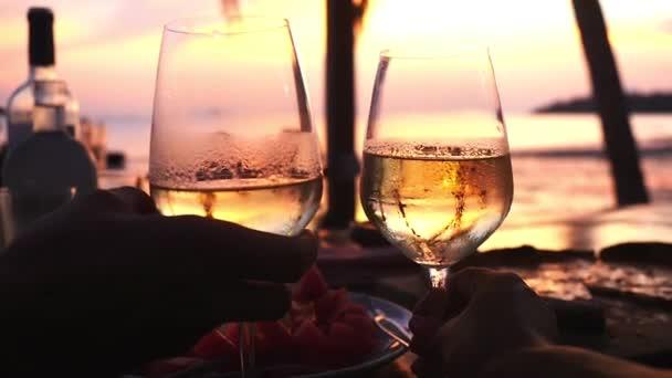 Vor dem Sonnenuntergang am Meer nimmt das Paar zwei Gläser mit Weißwein in die Hand. Zeitlupe, 1920x1080