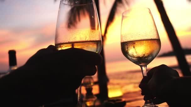 Klirrende Gläser mit Weißwein auf traumhaften Sonnenuntergang. HD, 1920 x 1080. Slow-motion