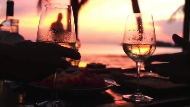 Pár v lásce cinkání sklenic s bílým vínem na úžasný západ slunce. HD, 1920 × 1080. Zpomalený pohyb
