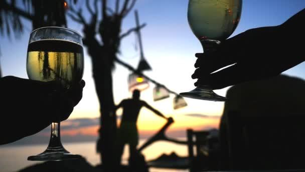 Paar klirrt nach Sonnenuntergang im Strandcafé mit einem Glas Wein. Zeitlupe. 1920x1080