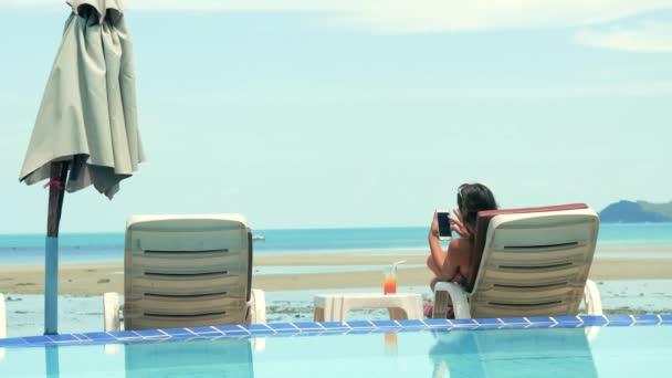 Krásná bruneta žena pomocí její telefon v plážové lehátko a take na opalování. 3840 x 2160