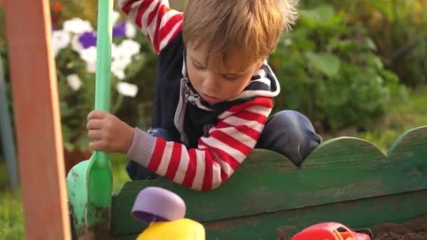 Piccolo bambino ragazzo giocando in sandbox sul parco giochi in giornata di sole