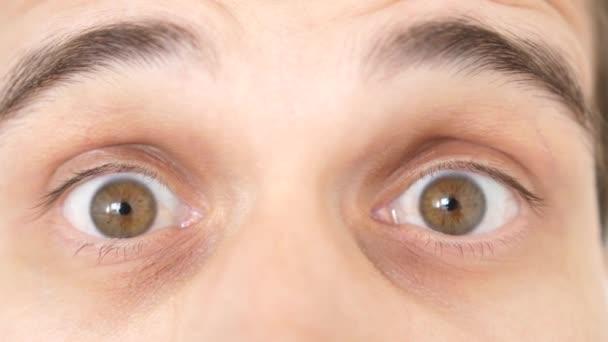 Zblízka překvapený zmatený emocionální muž s hnědýma očima, který hledí do kamery. Zpomaleně. 3840x2160