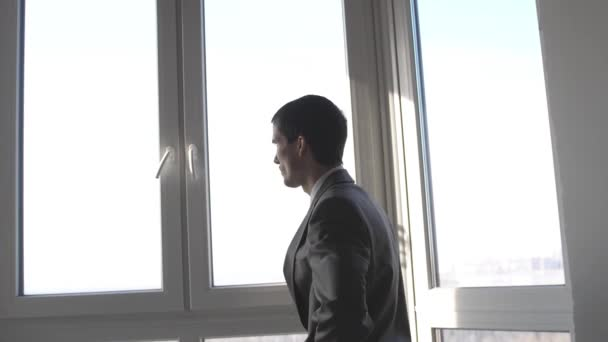 Young upset businessman standing in front of windows looking into distance on the city. slow motion. 3840x2160
