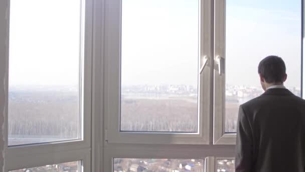 Pohled na mladého úspěšného obchodníka, který stál před okny a hleděl do dálky ve městě. Zpomaleně. 3840x2160