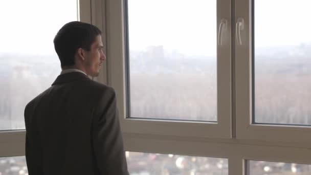 Mladý úspěšný podnikatel stojí před okny a dívá se do dálky na město. zpomalit. 3840x2160
