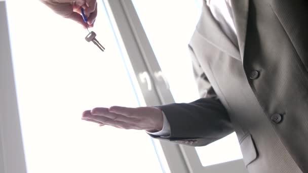Agente immobiliare che consegna una chiave a un cliente sullo sfondo della finestra e poi si stringe la mano. Rallentatore. 3840x2160, 4k