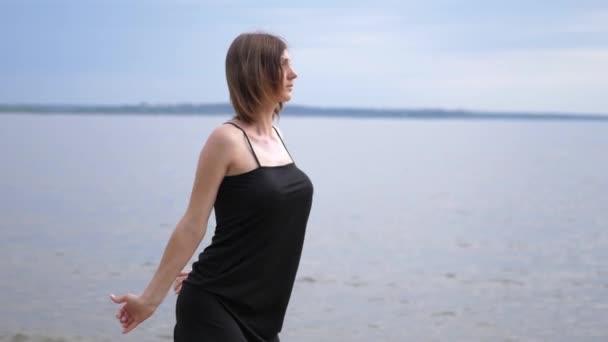 Junge schöne Frau tanzt an der Küste. Zeitlupe