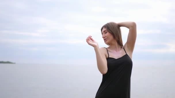 Mladá krásná žena tančí na pobřeží
