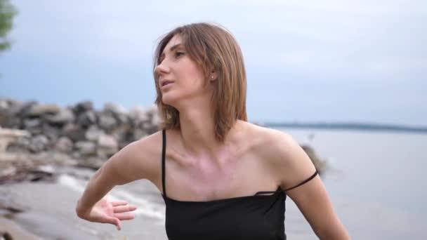 Junge schöne Frau tanzt am Meeresufer