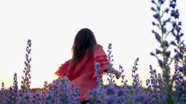 Mladá žena v červených šatech se těší v květinovém poli během západu slunce