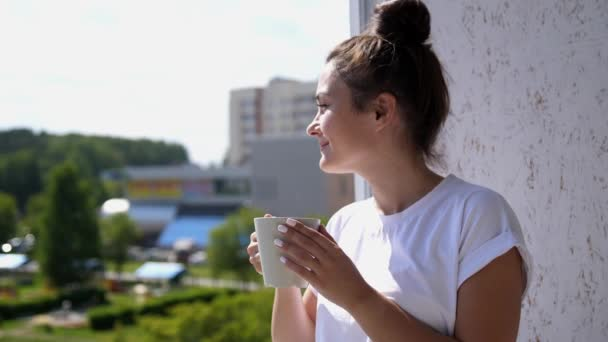 Pretty young woman on balcony drinks cup of coffee or tea watching a beautiful urban view and enjoy relax breathing fresh freezing air of summer. slow motion