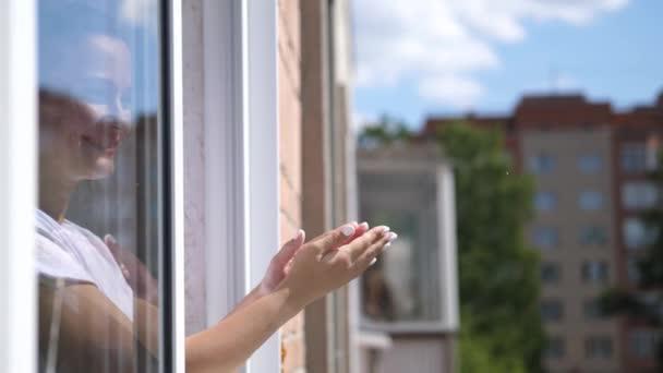 Žena v lékařské masce tleská rukama a dívá se z otevřeného okna. zpomalený pohyb