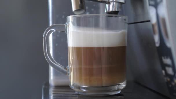 Női kéz tejeskávét iszik egy automatizált kávéfőző gépből..