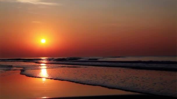 ruhiger goldener Sonnenaufgang über dem Meer