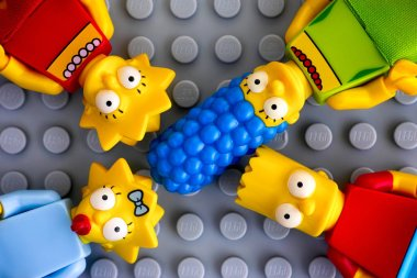 Tambov, Russian Federation - May 20, 2018 Four Lego Simpsons minifigures - Marge, Bart, Lisa, and Maggie, on gray background. Studio shot.