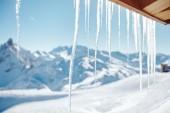 Fotografie Rampouchy visící ze střechy horské chatě proti zimní zasněženou krajinu lyžařské středisko ve francouzských Alpách - zimní svátky pozadí koncepce