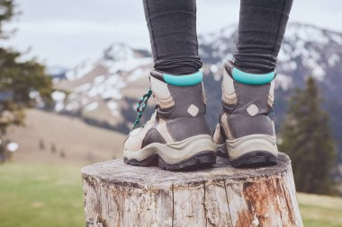 Close up of female classic leather hiking boots wearing by woman standing on stump in mountains - travel and outdoor activities concept