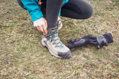 Close up of woman tying laces on her classic leather hiking boots on green grass - outdoor activities concept