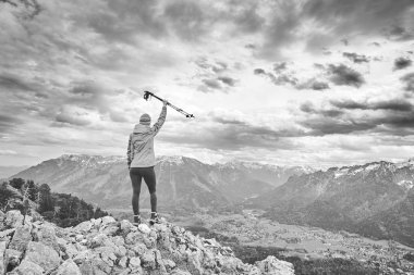 Black and white portrait of young female hiker with trekking poles in arm raised celebrating achievement standing on top of mountain after successful ascent - adventure, freedom or success concept