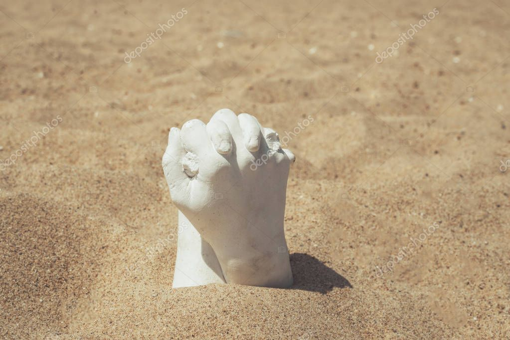 Two hands together made of plaster on the sand.