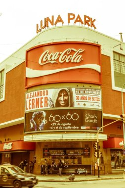 BUENOS AIRES, ARGENTINA - SEPTEMBER 20: A taxi pass in front of the famous Luna Park concert hall, on Corrientes street, Sunset in Buenos Aires, Argentina.   Vintage and yesteryear effect