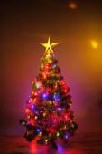 Vánoční stromek se slavnostními světly, oranžové pozadí