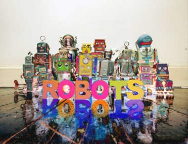 a team of vintage robots on a old wooden floor with the word ROBOTS  with wooden letters