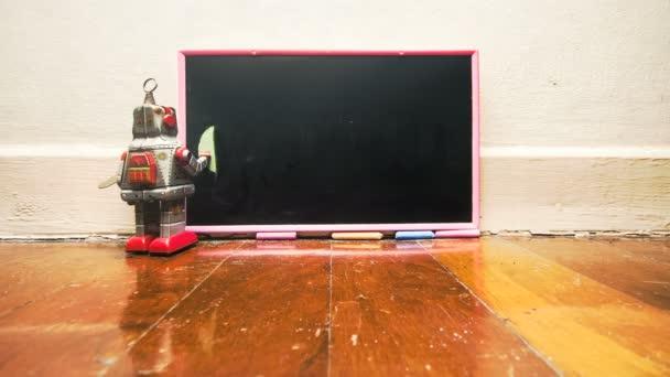 little robot writes CODING on a blackboard