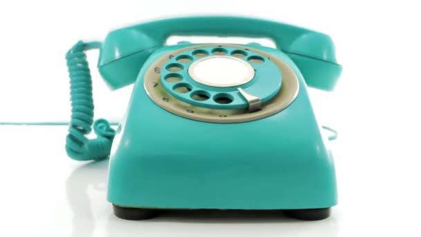 egy retro türkiz telefon cseng le a horogról, fehér alapon elszigetelve