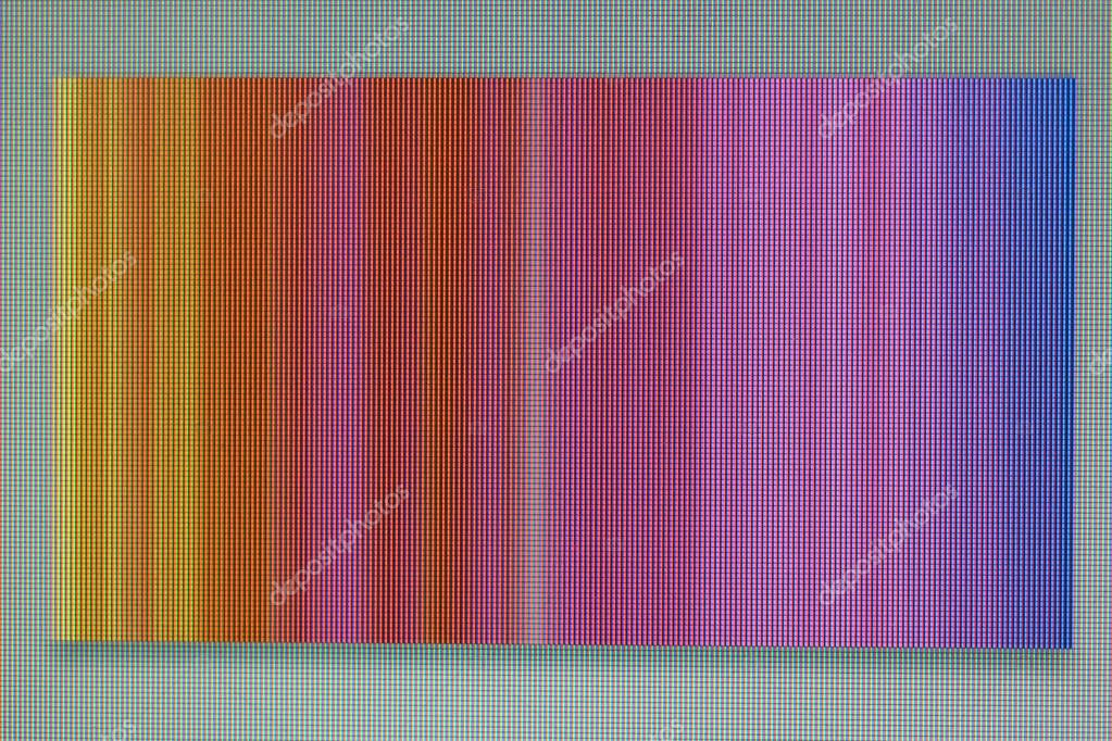 A macro photo of a chaotic colored striped noise on the monitor screen. A well-seen pixel structure