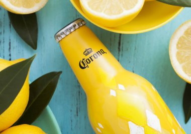 LONDON, UK - APRIL 27, 2018: Steel Bottle of Corona Extra Beer on blue wooden background with fresh lemons.Corona, produced by Grupo Modelo.