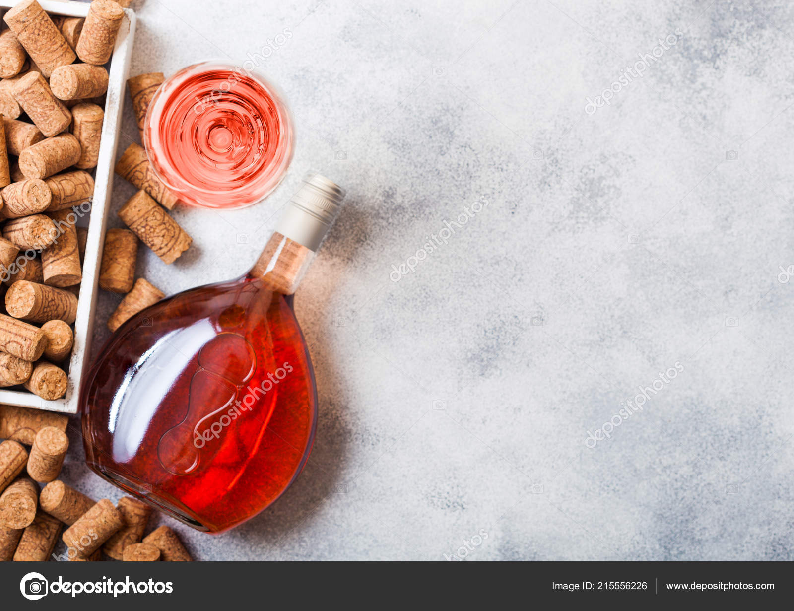 57faae41b30045 Bottle and glasses of pink rose wine with box of corks on stone kitchen  table background. Top view.– stock image
