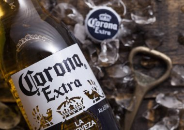 LONDON, UK - APRIL 27, 2018: Glass Bottle of Corona Extra Beer on wooden background with bottle opener and ice cubes. Corona, produced by Grupo Modelo.