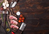 Čerstvé syrové řezníci jehněčí hovězí kotlety na prkénko s vintage maso sekeru a kladivo na dřevěné pozadí. Sůl, pepř a olej s rajčaty a česnekem a barbecue omáčkou