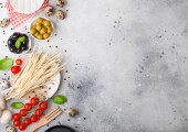 Homemade spaghetti pasta with quail eggs with bottle of tomato sauce and cheese on kitchen background. Classic italian village food. Garlic, champignons, black and green olives, pan and spatula.
