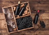 Photo Mini bottles of red wine and empty glasses with dark grapes with