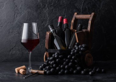 Elegant glass of red wine with dark grapes and mini bottles of wine inside vintage wooden barrel on black stone background. stock vector