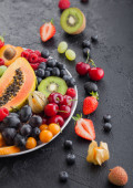 Fresh raw organic summer berries and exotic fruits in white plate on black background. Pineapple, papaya, grapes, nectarine, orange, apricot, kiwi, pear, lychees, cherry and physalis. Top view
