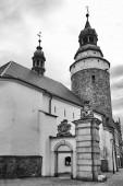 Středověký, kamenný kostel se zvonicí a fragmentem městské brány v Jelenia Gora v Polsku, černý a bílý