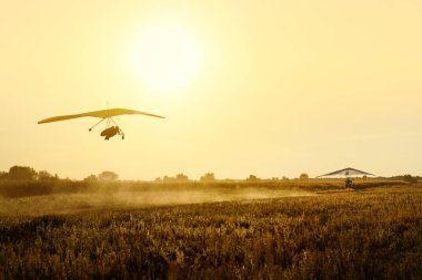 Two hang gliders tow on the sunset. Moody evening shot of extreme sport