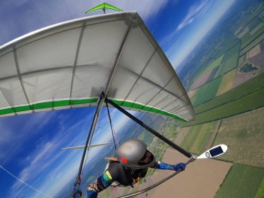 Hang glider pilot soar the thermal updrafts high over terrain. Action camera shot of extreme sport