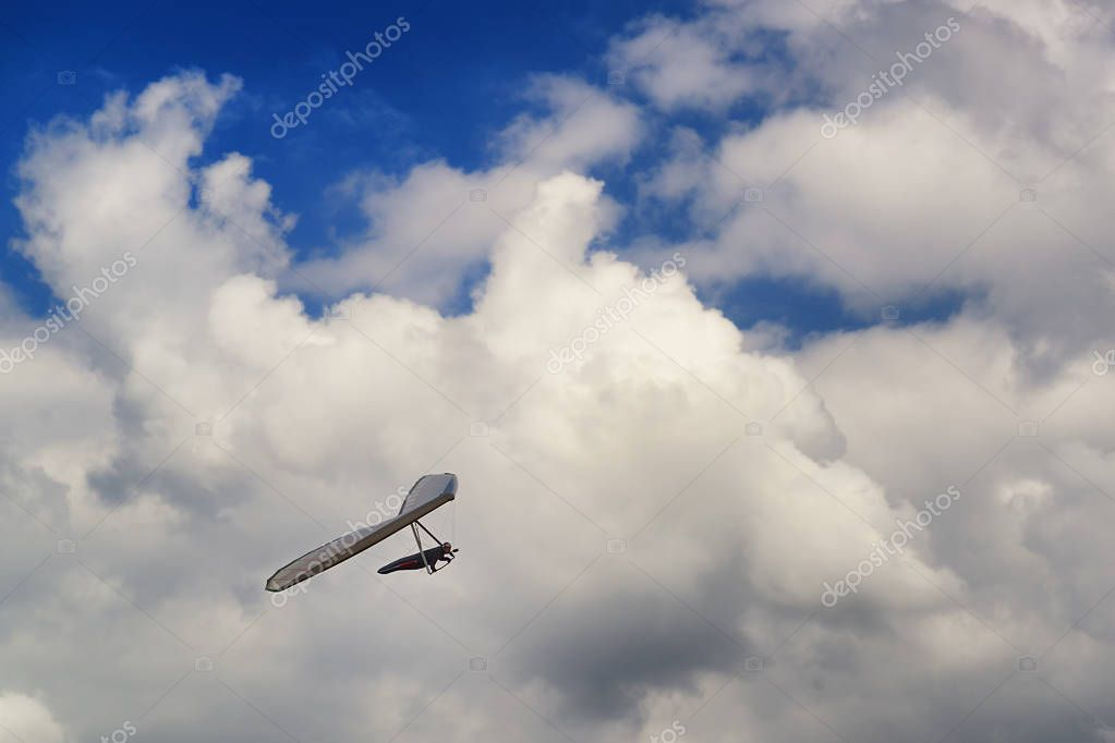 Hang glider pilot soar in thermal updrafts below the clouds. Vivid photo of man doing extreme sport