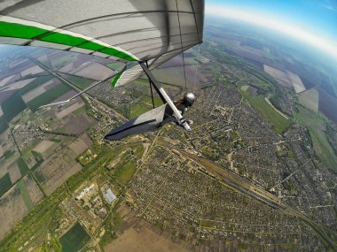 Hang glider pilot fly high above town and railroad station.
