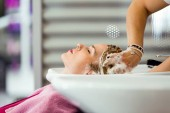 Shot of pretty young woman washes hair in a beauty salon.