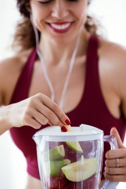Shot of sporty young woman making a smoothie while listening to music over white background.