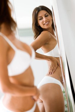 Shot of beautiful young woman in white underwear looking herself reflection in mirror at home.